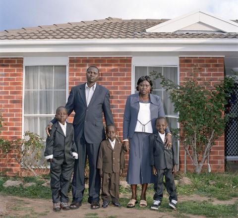 Sudanese family outside Australian home in formal wear