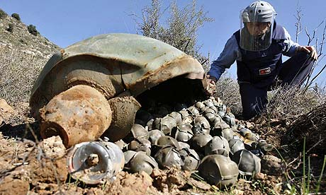 Photo of a Mines Advisory Unit inspector looking at a cluster bomb unit