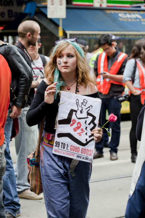 """An Occupy Melbourne protester with a sign saying """"99% to 1% Good Odds"""""""
