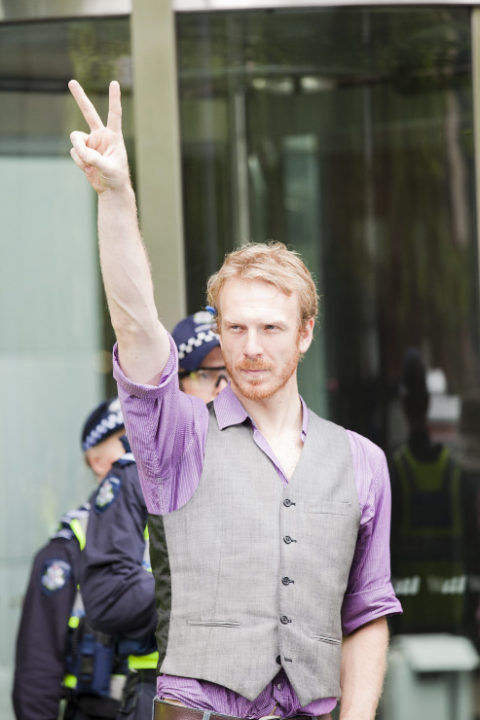 An Occupy Melbourne protester poses in front of BHP Billiton
