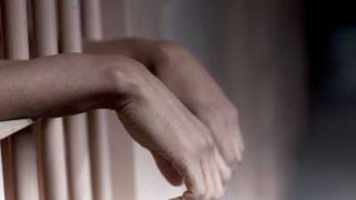 Photo of black hands behind bars