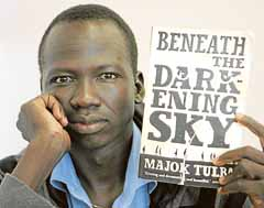 Sudanese refugee Majok Tulba with his novel, The Darkening Sky