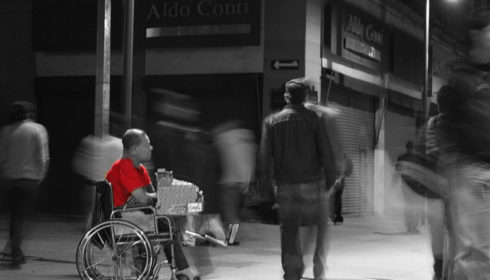 Man in wheelchair wearing red shirt, in black and white scene