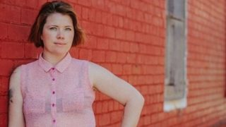 Clementine Ford wearing pink shirt standing in front of brick wall