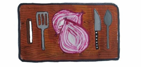 Halved red onion and cooking utensils on chopping board