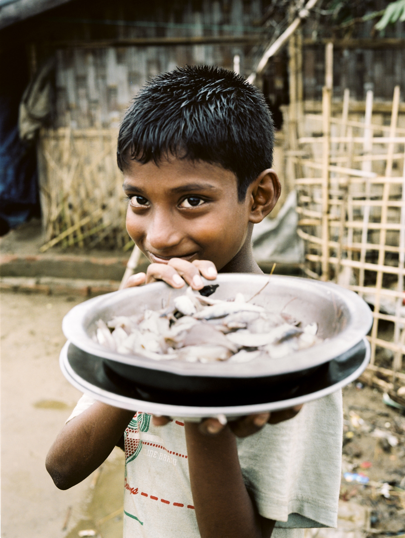 'Rohingya boy in IDP camp, holding fish caught from a nearby river' - Fighting continues in Western Myanmar, with reports of massacres and atrocities of Rohingya people by government forces. With little international support, the Rohingya essentially remain trapped in between the two countries, with neither recognising them as citizens. As such, the Rohingya remain a persecuted, stateless people with nowhere to go.