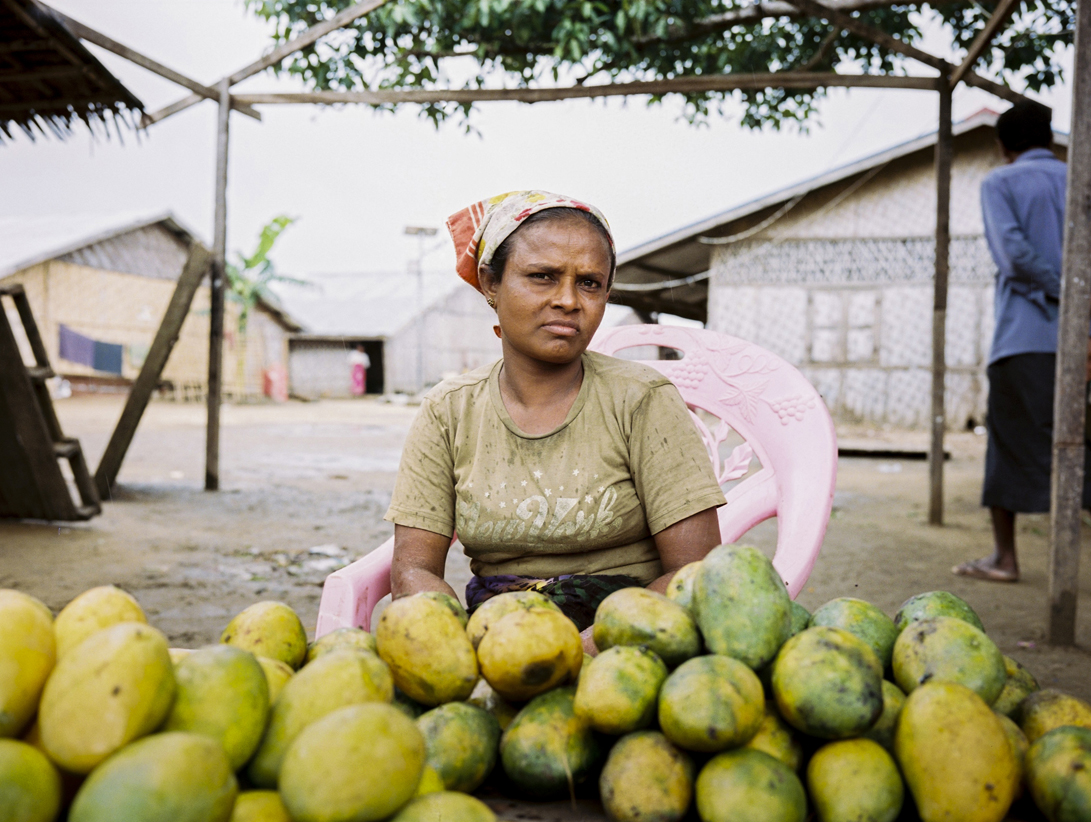 Rohingya are believed to have migrated from 'Rohingya woman selling mangos at market stall' - Bengal to the area formerly known as Arakan in the 1600's, with increased migration occurring during British colonial rule. After independence in 1948, the Rohingya essentially became stranded in what was then known as Burma.