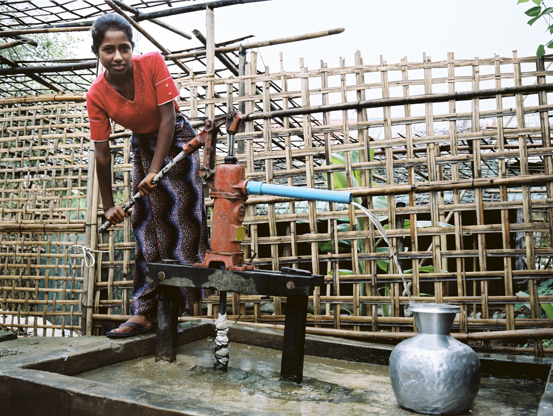 'Rohingya girl pumping water for the family' - Conditions in the camps are dire, with electricity generated by donated solar panels and water pumped from communal wells. Entire families of up to 10 people live in leaky one-room bamboo huts.