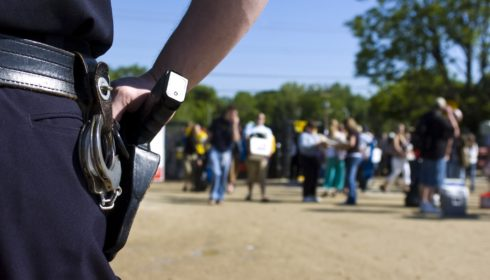 A police officer watches as spectators enter the a large public event, focus on handgun.