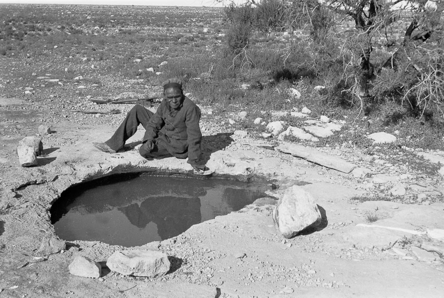 Tracker Jimmie Maadi sits next to the rockhole where Cundeelee mission was based. This water supply was known as Urpulurpulila by Anangu, which means 'tadpole' in Pitjantjatjarra language. It was by way of rock holes such as this, as well as other sources of water, that Anangu could survive in the harsh desert climate.