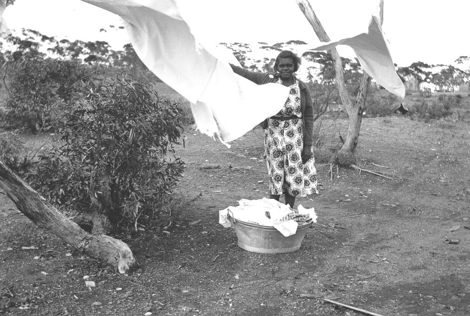 Marjorie Watson hanging out the mission washing in Cundeelee. Anangu women were often given households chores to do as part of mission life, as part of the assimilation process, and were often sent to farms to work as household labourers, for which they were never paid.