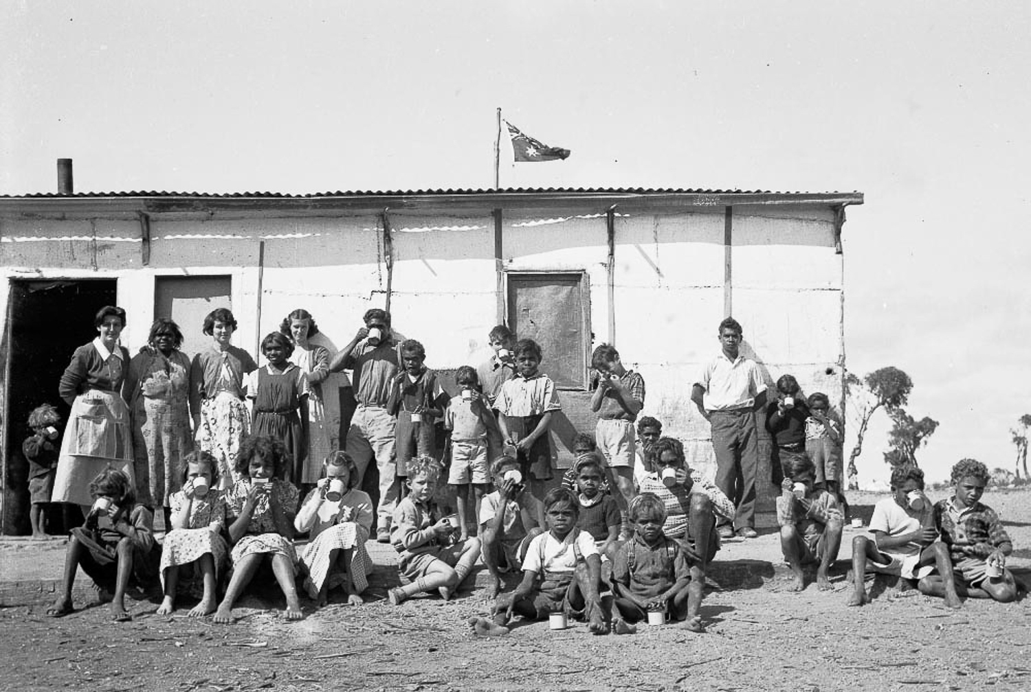 'Cocoa time' at Cundeelee mission, outside the kitchen under the Australian flag. The Cundeelee mission would be eventually closed in 1985, and in 1986, elders would return to their original homelands on Spinifex Country to the east, and establish the community of Tjuntjuntjara.