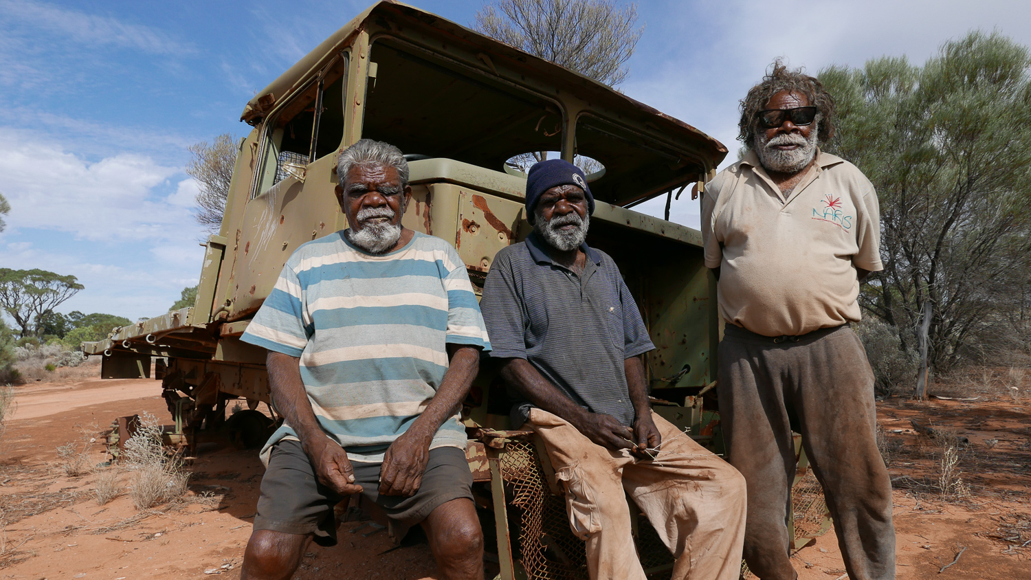"""Fred Grant, Rusty Hogan and Ned Grant, with the army truck they travelled in to return to Spinifex Country and establish Tjuntjuntjara community. Fred and Ned were part of the original group of people who were 'found' in the bush and relocated to Cundeelee mission. In the late 1980's they returned to Spinifex Country, because they """"wanted to be home"""", and to be able to continue to speak their original language and practice their culture."""
