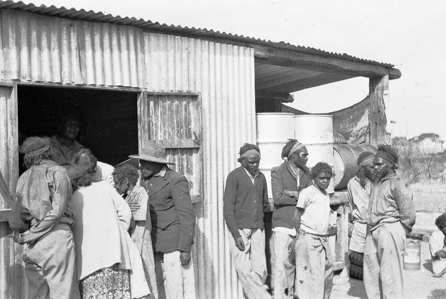 Jack Jamieson, Albert Jamieson, Frank Hogan, Arthur Jamieson and Bill Jamieson stand huddled together on the right, newcomers to the mission at Cundeelee. While the forced relocation of Anangu saw them dislocated from their homelands, descendants are grateful to the trackers who located them, as they were saved from potential disaster from the nuclear testing and a prolonged draught in Spinifex Country.