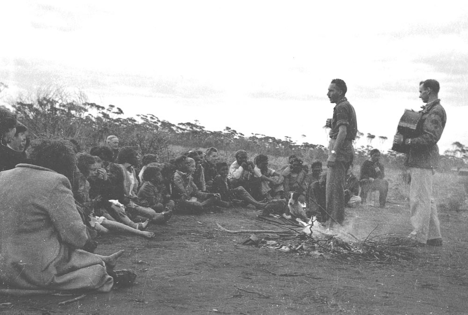 A church camp meeting at Cundeelee, led by missionary, teacher and photographer Robert McKeich. Anangu would set up bush camps around the mission site, and would be visited by missionaries who would hold church services in an attempt to convert Anangu to Christianity.