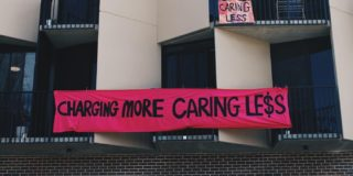 "Black and cream building with grey bricks and a pink banner in the centre that reads ""Charging more caring less"""