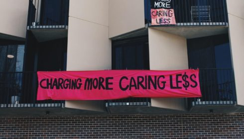 """Black and cream building with grey bricks and a pink banner in the centre that reads """"Charging more caring less"""""""