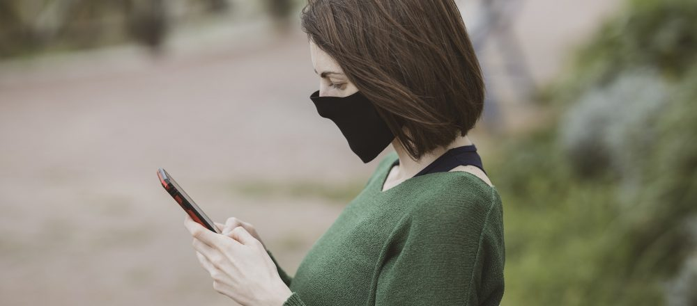 woman in mask using phone