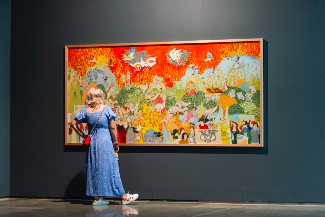 A person standing in front of a painting  Description automatically generated with medium confidence